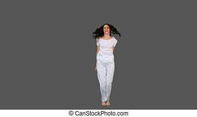 Content young model in pyjamas exercising on grey background