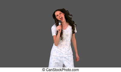 Happy young model in pyjamas singing on grey background