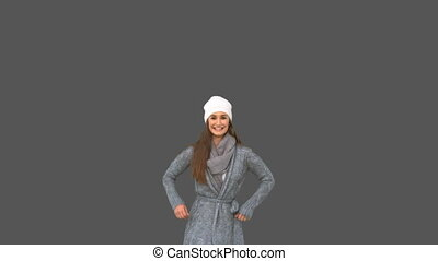 Cheerful young model in winter clothes jumping on grey...