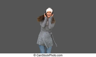 Cheerful young model in winter clothes listening to music on...