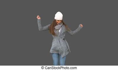 Cheerful young model in winter clothes dancing on grey...