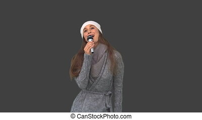Cheerful young model in winter clothes singing on grey...