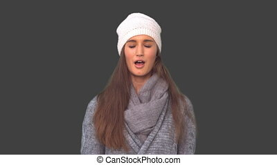 Young model in winter clothes sneezing on grey background