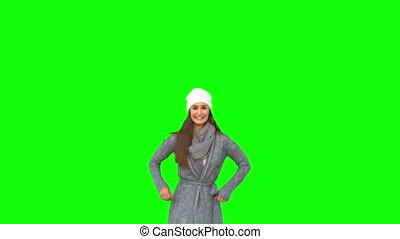 Happy young model in winter clothes jumping on green...