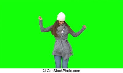 Happy young model in winter clothes dancing on green...