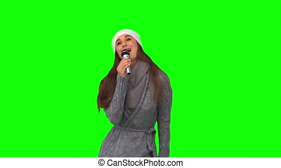 Happy young model in winter clothes singing on green...