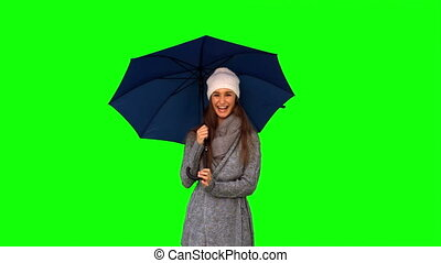 Happy young model in winter clothes playing with umbrella on...