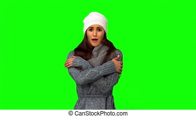 Pretty model in winter clothes shivering on green background