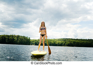 teen girl stand up paddle boarding on a lake in haliburton...