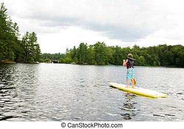 young boy stand up paddle boarding