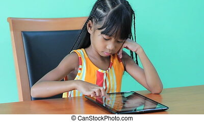 Girl Playing Game On Digital Tablet - A cute little seven...