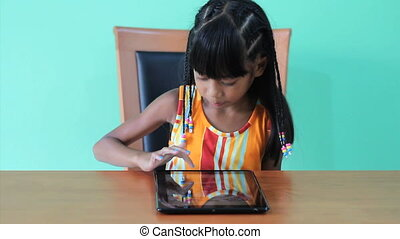 Girl Playing Game On Digital Tablet - A cute seven year old...