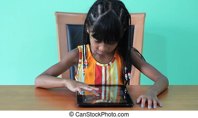 Happy Asian Girl On Digital Tablet - A cute seven year old...