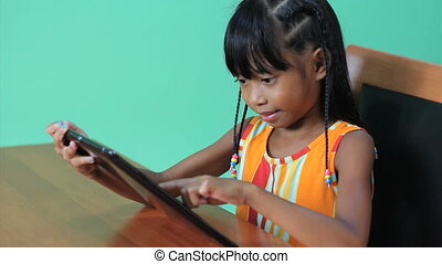 Asian Girl Uses Digital Tablet - A cute seven year old Asian...