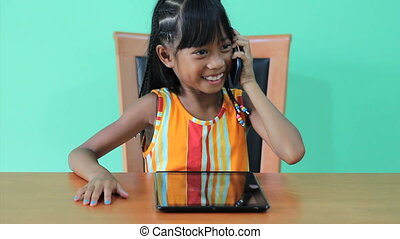 Asian Girl Talks On Smart Phone - A cute little seven year...