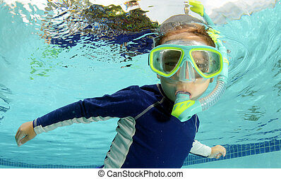 child snorkeling and swimming in pool
