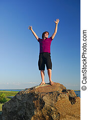 Achievement - A young man celebrates achievment in a nature...