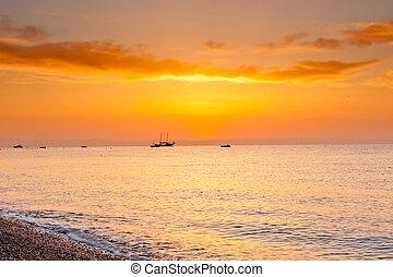 sunrise over the calm sea in orange tones