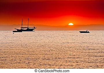 red sunset behind the mountains over the sea and ships