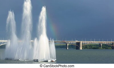 Fountain - Rainbow hanging over river fountain.