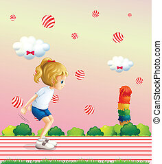 A girl playing at the field with candy balls floating