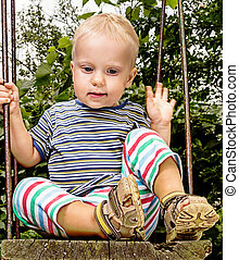 Boy on swing - Baby boy 1 year sitting on swing outdoors
