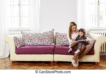 Mother and daughter reading in the room
