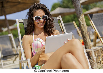 Young woman with tablet on the beach