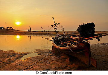 The old fishing boat and sunset on the beach Phangnga