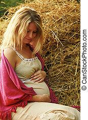 Pregnant spokeswoman nature near haystack - a Pregnant...