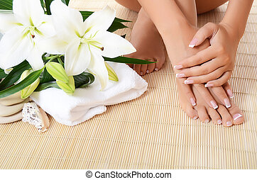 Woman hand and feet with manicure and Lily - Woman hand ,...