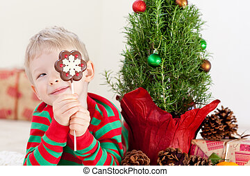 christmas time - little smiling boy holding a candy at...