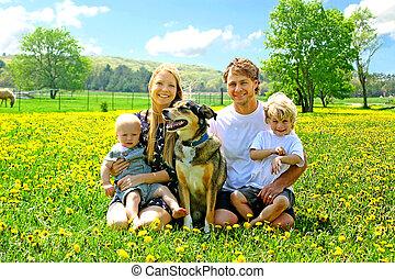 Happy Family Sitting In Dandelion Field - a happy family of...