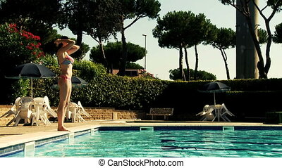 Gorgeous woman jumping in pool