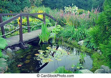 A pond with water-lilies and wooden bridge in a city park on...