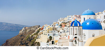 Santorini panorama - Blue domed church in Oia overlooks the...