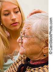 Trust - A young woman patting an older one whit trust and...