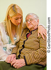 Trust - A young woman holding an older one whit love and...