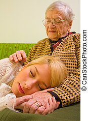 Calmness - A young woman sleeping on her grandmothers feet -...