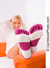 Socks 2 - A beautiful young woman sitting on her bed,...
