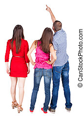 Back view of three friends pointing man and two women...