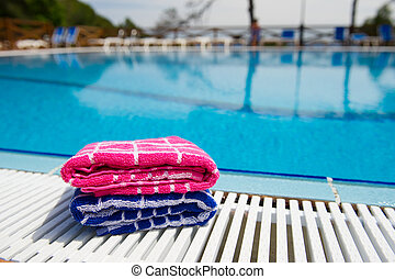 Towels at swimming pool - Stacked pink and blue towels at...