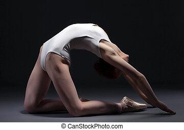 Portrait of graceful ballerina posing in studio