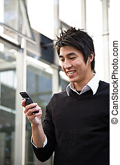 Texting casual asian businessman - A casual asian...