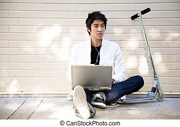 Young casual asian man with laptop - A young casual asian...