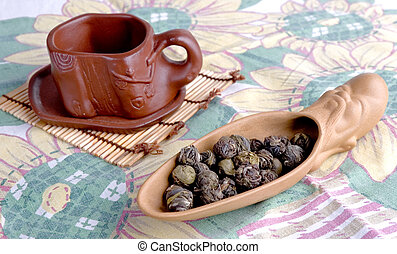 loose leaf tea - clay spoon with loose leaf tea and cup of...