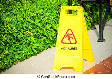 """warning label """"Wet floor"""" yellow on the tile floor"""