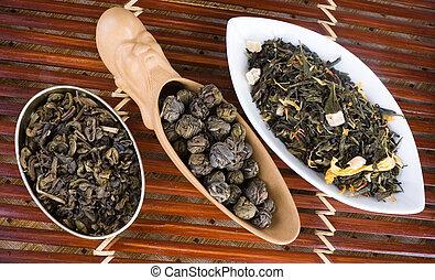 loose leaf tea - three different heaps of loose leaf tea in...