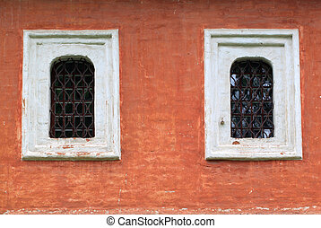 Two windows with bars on the red wall