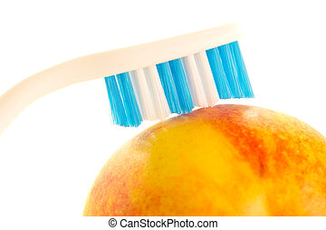 Toothbrush on fruit - A blue toothbrush lying ontop of a...